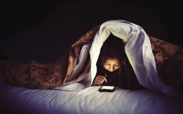 Kuvassa teini valvoo salaa yöllä peiton alla ja puhelimen valo loistaa silmiin.