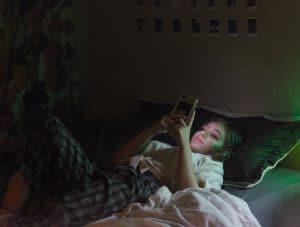 Pimeässä huoneessa makaava nuori pitelee puhelinta kasvojensa edessä, joita sinivalo valaisee.
