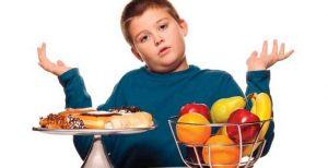 Esillä on kaksi tarjotinta. Toisella on rasvaisia ja makeita herkkuja, toisella hedelmiä. Tarjottimen äärellä oleva lapsi levittelee käsiään sen näköisenä, ettei tiedä, kumpia ottaisi.