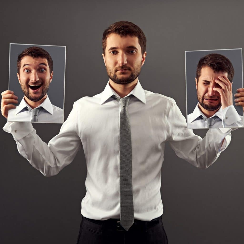 Kuvassa on mies, jonka mieliala vaikuttaa neutraalille. Hän pitää käsissään kahta valokuva kasvoistaan, joista toisessa hän itkee (masentunut) ja toisessa on riehakas (maaninen).