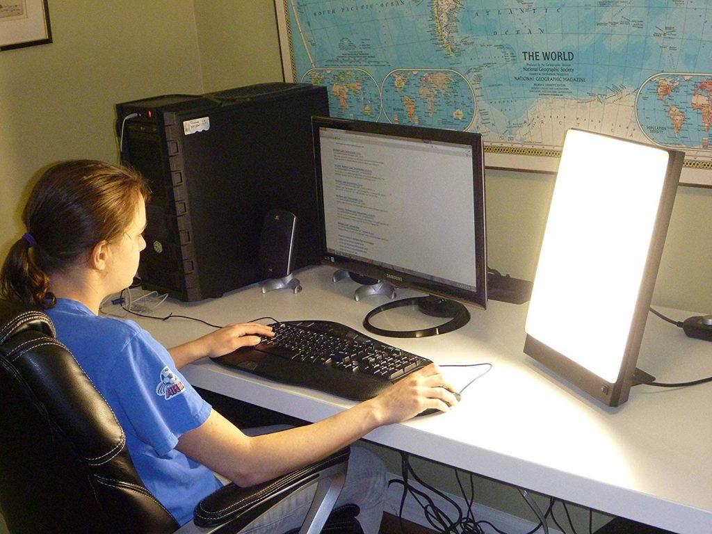Nuori tyttö istuu työpöytänsä äärellä kirkasvalolamppu edessään ja hyödyntää ajan olemalla samalla netissä.