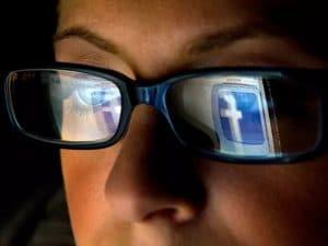 Kasvojen lähikuvassa silmälaseista heijastuu Facebookin logo.