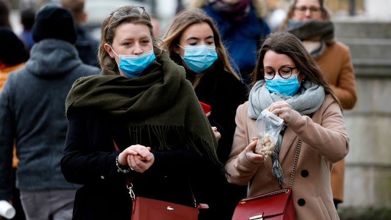 Kuvassa ihmisjoukko, jonka etualalla on kolme naista, joista jokaisella on suu- ja nenämaski kasvoillaan.