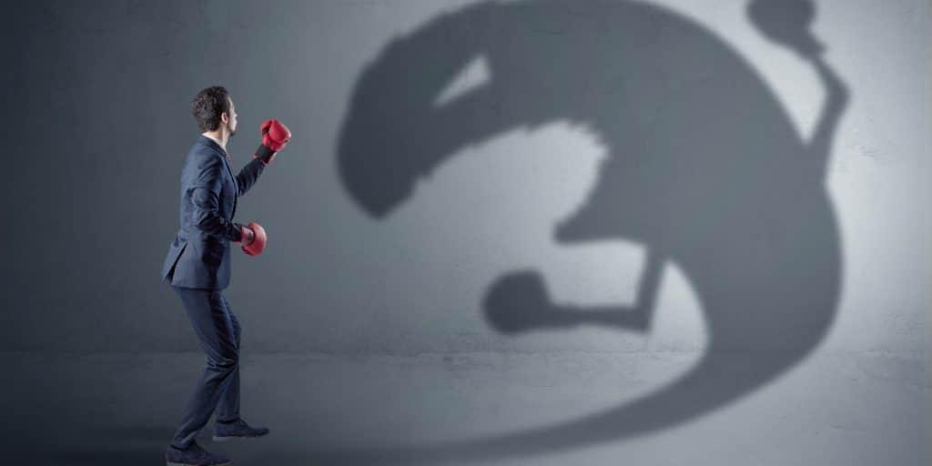 Punaisiin nyrkkeilyhanskoihin pukeutunut mies taistelee varjoa vastaan, myös varjolla on nyrkkeilyhanskat.