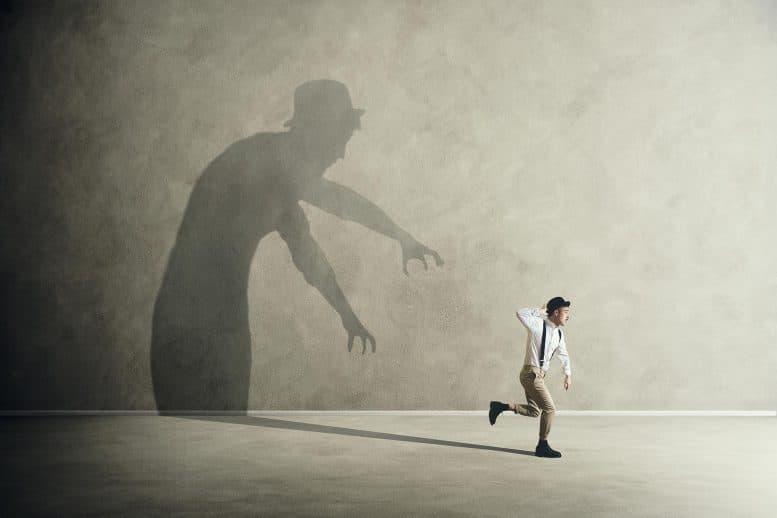Charles Chaplinin näköinen hahmo juoksee karkuun seinällä olevaa varjoa, joka profiilin perusteella on juoksija itse.