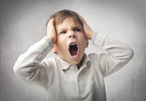 Vihainen lapsi huutaa päätään pidellen.