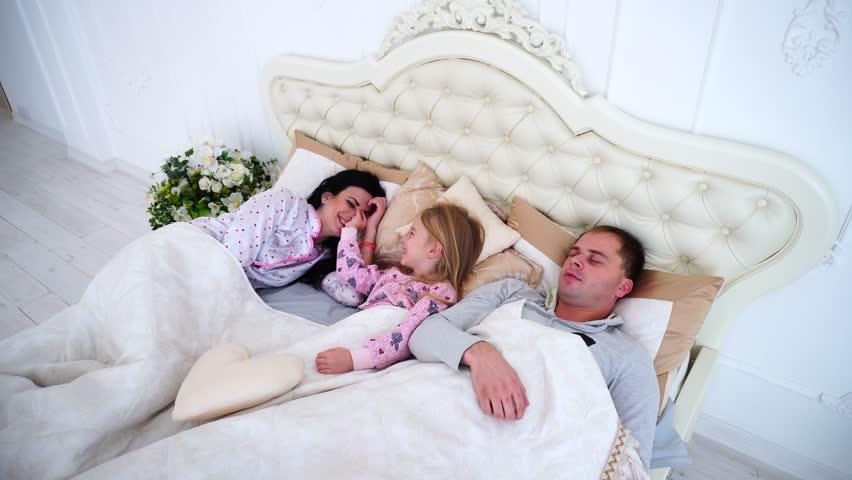 Vanhemmat nukkuvat parisängyssä, kun heidän väliinsä tullut lapsi herättää heidät. Pyjamat ovat luonnollisesti päällä.