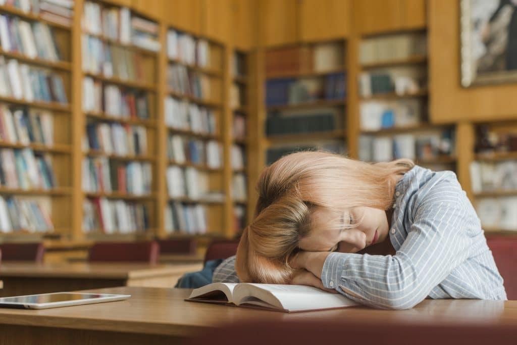 Nuori nainen nukkuu ja hänen päänsä on avoinna olevan kirjan päällä. Ympäristönä on kirjasto.