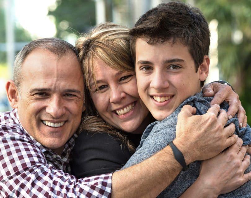 Äiti, isä ja teini-ikäinen poika ovat tiukassa halauksessa, kaikilla on iloinen ilme kasvoillaan. Syntyy vaikutelma lämpimästä suhteesta, jossa läheisyyskään ei pelota.