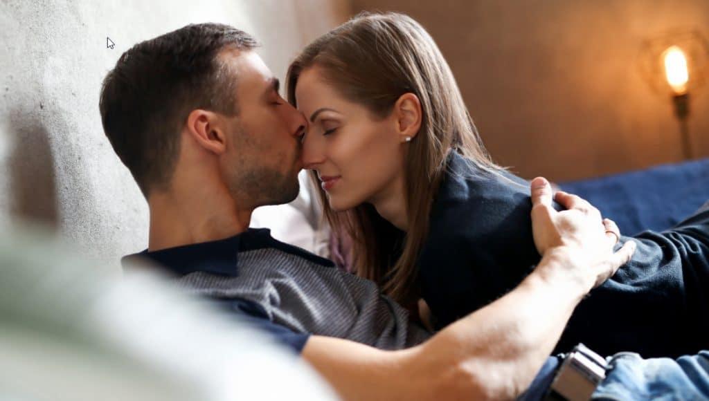 Pariskunta on vuoteessa, mies suutelee naista kasvoille. Kuvan fiilis on lämmin, ja vaatteet ovat toki yllä.