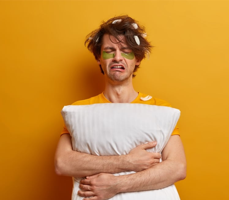 Mies pitää tyynyä sylissään. Tyynyn höyhenet ovat takertuneet mm. miehen hiuksiin. Ilmeen perusteella mies on romahtamassa. MIssä on psykologisen ahdingon ja fysiologisen stressin raja?